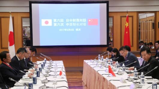China's Finance Minister Xiao Jie (R) talks with his Japanese counterpart Taro Aso (L) during their meeting in Yokohama, near Tokyo, on May 6, 2017.