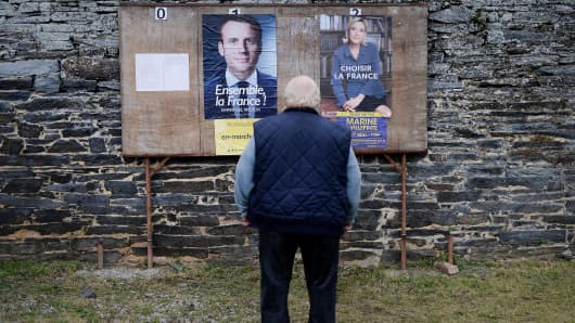 A man stands in front of posters during the second round of the French presidential election in the town of Saint-Sulpice-des-Landes, western France on May 7, 2017.