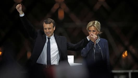 French President elect Emmanuel Macron and his wife Brigitte Trogneux celebrate on the stage at his victory rally near the Louvre in Paris, France May 7, 2017.