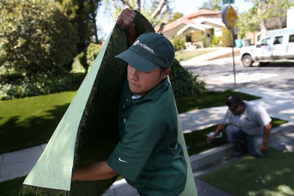 An employee of the Onelawn landscaping company installs a section of artificial lawn at a home in Burlingame, California.
