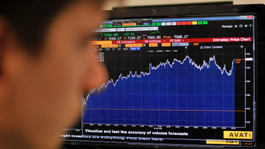 A journalist looks at the Intraday Price Chart showing London's FTSE 100 Index.