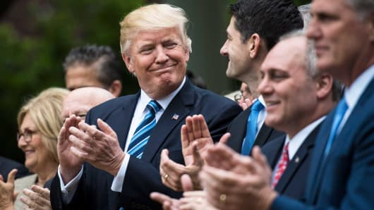 President Donald Trump looks to House Speaker Paul Ryan and other House congressmen in the Rose Garden after the House passed a health care bill, at the White House in Washington, DC, May 04, 2017.