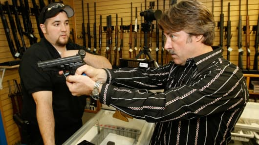 A gun store sales associate looks on as a customer tries out a semi-automatic pistol in Las Vegas, Nevada.