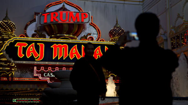 The silhouettes of visitors are seen taking photograph outside the Trump Taj Mahal casino and hotel, owned by Trump Entertainment Resorts Inc., in Atlantic City, New Jersey, U.S., on Sunday, May 8, 2016.
