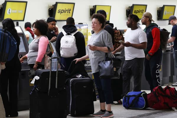 People stand in line to check in at the Spirt Airlines counter at the Fort Lauderdale-Hollywood International Airport on May 9, 2017 in Fort Lauderdale, Florida.