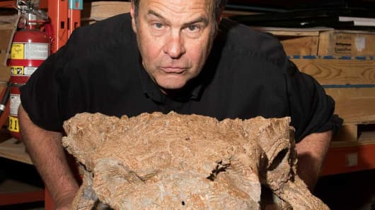 """Actor Dan Aykroyd poses in the Royal Ontario Museum's paleontology collections room with fossils of Zuul crurivastator, a new species of armored dinosaur named after the beast Zuul from the film """"Ghostbusters"""" at the Royal Ontario Museum in Toronto, Canada on on April 21, 2017."""