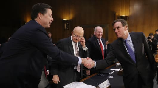 Mark R. Warner (D-VA), Vice Chair of the Senate Select Committee on Intelligence, greets FBI Director James Comey, Director of National Intelligence James Clapper and Central Intelligence Agency Director John Brennan (L-R) before they testify before the Senate (Select) Intelligence Committee in the Dirksen Senate Office Building on Capitol Hill January 10, 2017 in Washington, DC.