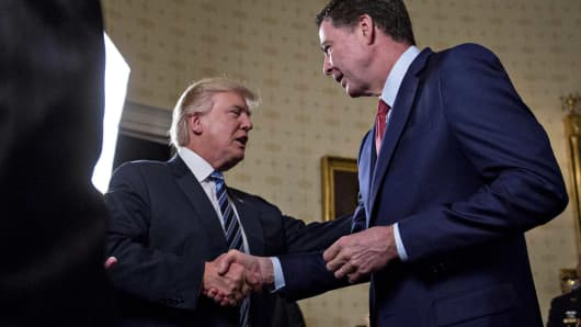 President Donald Trump, shakes hands with James Comey, then-director of the Federal Bureau of Investigation, during an Inaugural Law Enforcement Officers and First Responders Reception in the Blue Room of the White House in Washington, D.C., Jan. 22, 2017.
