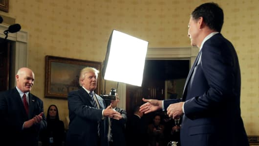 President Donald Trump greets Director of the FBI James Comey as Director of the Secret Service Joseph Clancy (L) watches during the Inaugural Law Enforcement Officers and First Responders Reception in the Blue Room of the White House in Washington, U.S., January 22, 2017.