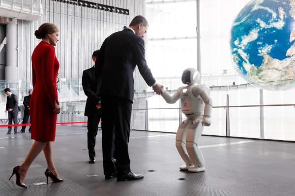 King Felipe VI shakes hands with an ASIMO robot.