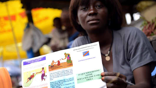 A vegetable's seller holds a Congolese Ministry of Health's information leaflet on Ebola virus on September 17, 2014 on Moral's market in the Bandal area in Kinshasa.