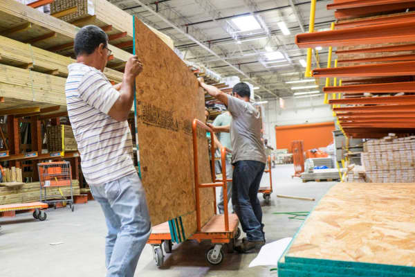 Shoppers selecting plywood in a Home Depot store in Miami.