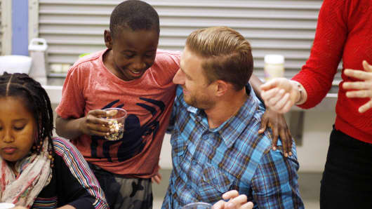 Uber head of global operations Ryan Graves (R) eats with fourth grader Frederick Dozier during Cooking Matters, a nutrition class taught by 18 Reasons, a local partner of Share our Strength at Glen Park Elementary School in San Francisco, California, December 10, 2014.