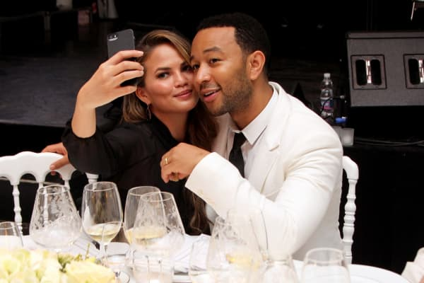 Chrissy Teigen and John Legend attend the White Party Dinner benefiting The Andrea Bocelli Foundation and The Muhammad Ali Parkinson Center.
