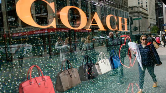A woman walks past Coach bags in a window of Macy's flagship store, May 12, 2017 in the Herald Square neighborhood in New York City.