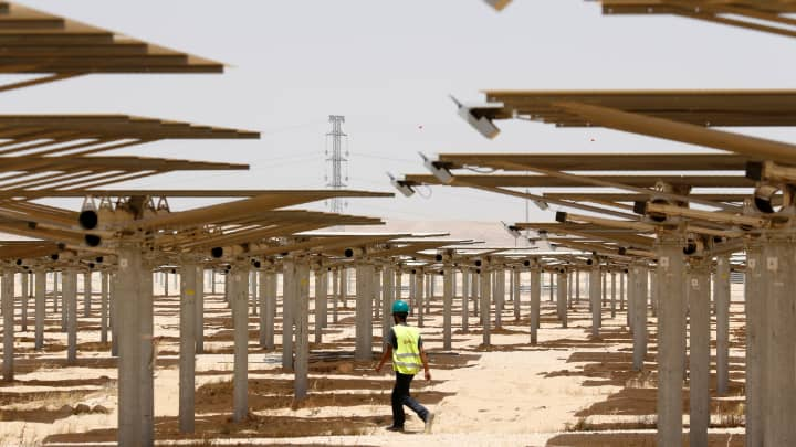 A worker walks past some of the 55,000 mirrors directing sunlight toward the Ashalim solar tower, which is under construction near the southern Israeli kibbutz of Ashalim in the Negev desert, on May 26, 2016.