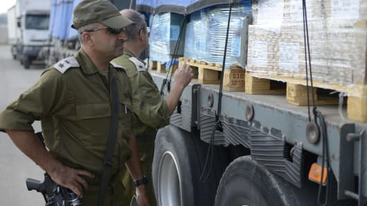 An Israeli military officer inspects a supply shipment into Gaza.