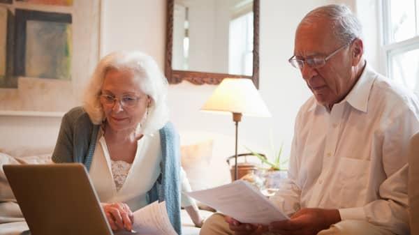 Senior couple using latop in home.
