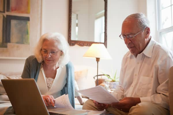 Senior couple using latop in home.