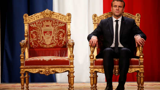 French President Emmanuel Macron listens as Paris Mayor Anne Hidalgo delivers her speech during a ceremony at the Hotel de Ville in Paris.