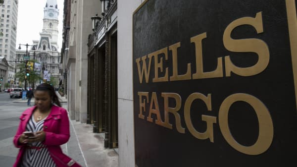 A woman walks past a Wells Fargo location in view of City Hall, left, in Philadelphia, Thursday, May 11, 2017. Philadelphia's city council approved legislation to remove Wells Fargo as the bank handling the city's payroll. Thursday's legislation authorizes Citizens Bank to handle those services at the start of the next fiscal year in July.