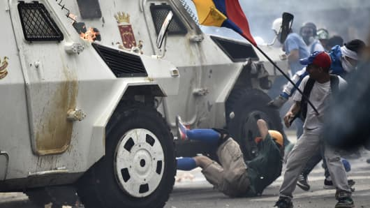 A charging National Guard riot control vehicle knocks down a demonstrator during a protest against Venezuelan President Nicolas Maduro, in Caracas on May 3, 2017.