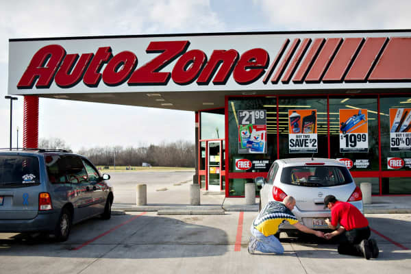 An employee, right, helps a customer change a license plate bulb outside an AutoZone store in Princeton, Illinois.