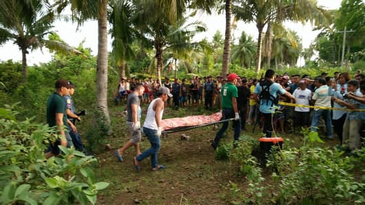 May 15, 2017: Philippine policemen (L) escorting funeral parlor employees carried the body of the second of the two Abu Sayyaf militants killed in an encounter with troops in Calape town, Bohol province.