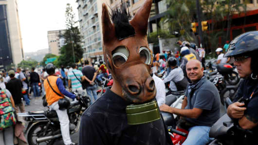 An opposition supporter uses a tear gas mask inside a mask of an ass during a rally against Venezuela's President Nicolas Maduro in Caracas, Venezuela, April 26, 2017.