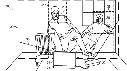 Apple's illustration for a 3D depth mapping system. A device, attached to the right of a screen, scans a room featuring two people.