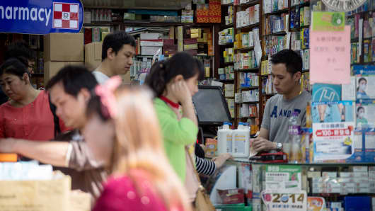 Customers browse merchandise at a pharmacy in the Sheung Shui district near the border with mainland China, in Hong Kong, China.