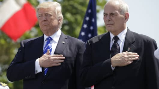 President Donald Trump (L) and U.S. Department of Homeland Security Secretary John Kelly hold their hands over their hearts for the U.S. National Anthem as they attend the Coast Guard Academy commencement ceremonies where Trump is addressing the graduating class in New London, Connecticut, U.S. May 17, 2017.