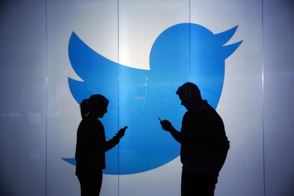 The Twitter logo is seen behind two people looking at their phones.