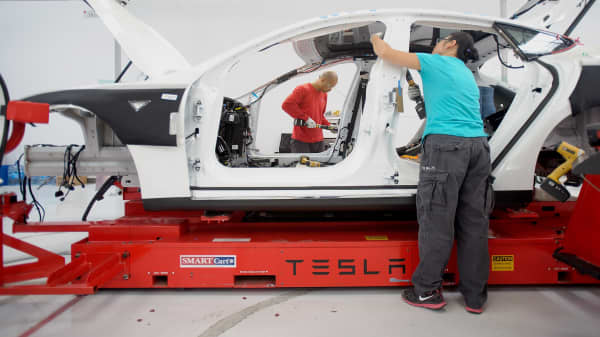 Workers add seat belts to a Tesla car at the assembly plant in Fremont, California.