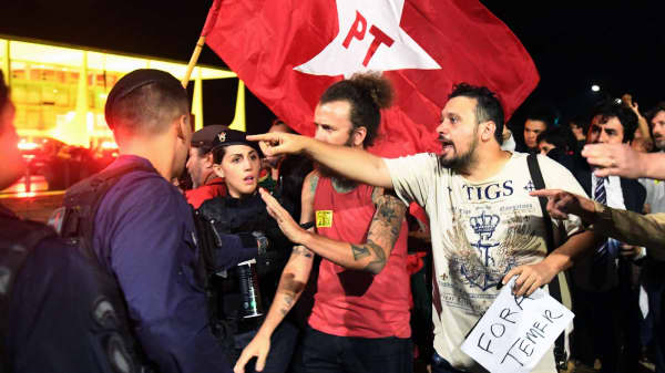 Demonstrators and police argue during a protest against Brazilian President Michel Temer outside the Planalto Palace in Brasilia on May 17, 2017.