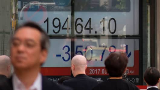 A pedestrian walks past a stock quotation board flashing the key Nikkei index of the Tokyo Stock Exchange in front of a securities company in Tokyo on May 18, 2017.