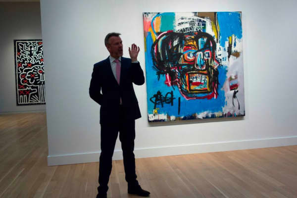 A Sotheby's official speaks about an untitled painting by Jean-Michel Basquiat during a media preview May 5, 2017 at Sotheby's In New York.