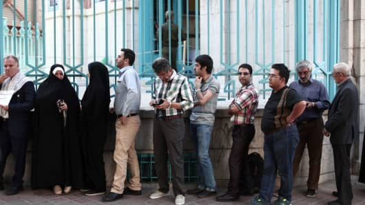 Iranians wait in a queue for the opening of the polling station to cast their ballots for the presidential elections in Tehran on May 19, 2017.