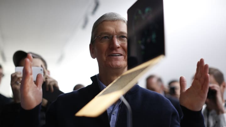 Apple CEO Tim Cook stands in front of an MacBook on display after an Apple special event at the Yerba Buena Center for the Arts on March 9, 2015 in San Francisco, California.