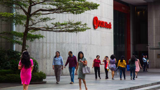 Pedestrians walk past an OCBC branch in the central business district of Singapore, on Friday, Feb. 10, 2017.