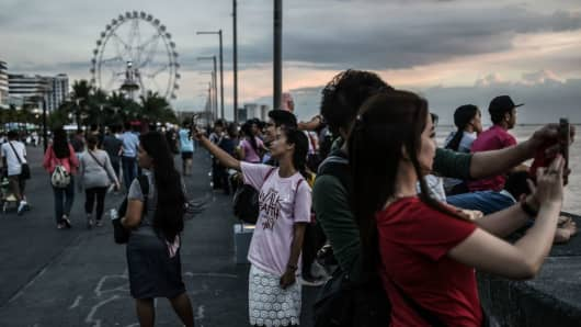Filipinos take pictures during sunset in Manila, the Philippines on April 26, 2017.