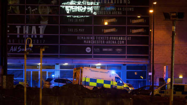 A police van and an ambulance are seen outside the Manchester Arena, where U.S. singer Ariana Grande had been performing.