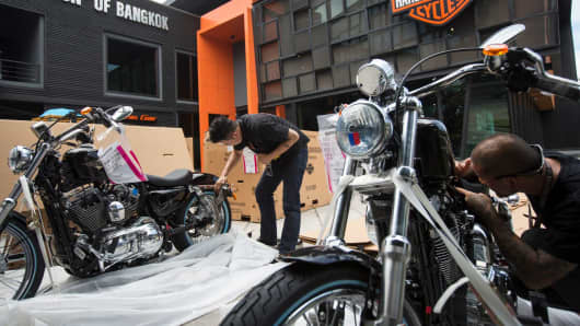 Workers examine new motorcycles arriving at a Harley-Davidson showroom in Bangkok, May 15, 2017.