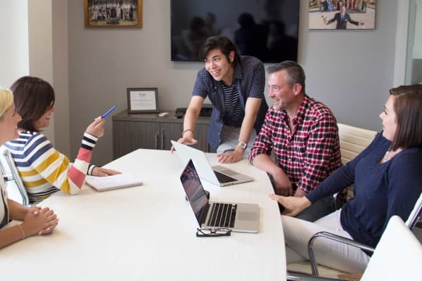 Jon Salas, standing, left a higher-paying job at a multinational HR company with a 'cardboard dry culture' to join Hollywood PR, where weekly brainstorming sessions bring the small team together.