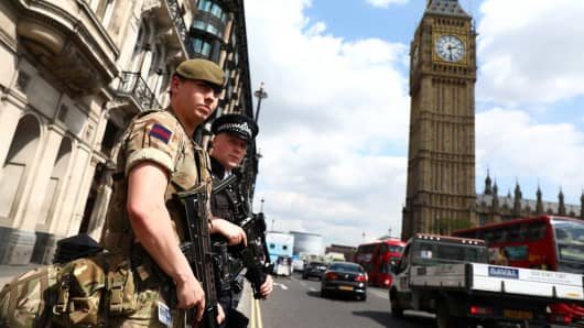 A soldier and an armed policeman pass Big Ben in London, Britain May 24, 2017.