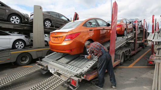 A worker secures the wheels of an Hyundai Accent vehicle onto the back of a transporter truck during loading ahead of distribution at the Hyundai Motors automobile plant in St Petersburg, Russia.