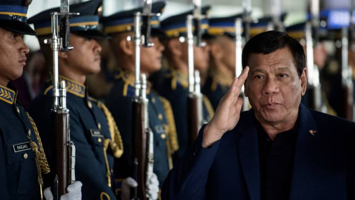 Philippine President Rodrigo Duterte walks past honor guards as he arrives at Manila international airport in Manila on May 24, 2017, after returning from a visit to Russia. Duterte threatened on May 24 to impose martial law in Mindanao to combat the rising threat of terrorism, after Islamist militants beheaded a policeman and took Catholic hostages while rampaging through a southern city.