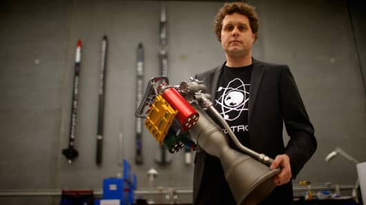 RocketLab founder Peter Beck holds his battery-powered rocket engine printed on 3D parts.