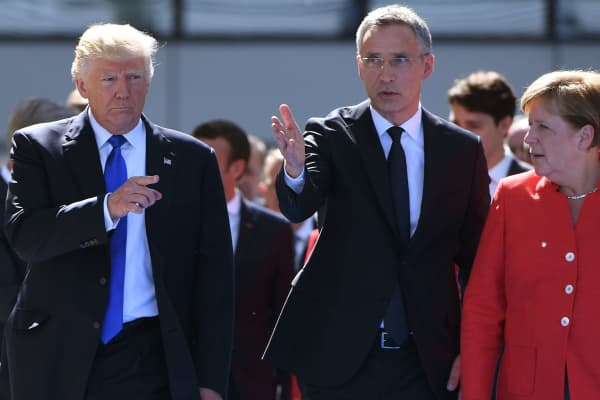 NATO Secretary General Jens Stoltenberg (C) speaks with US President Donald Trump (L) and German Chancellor Angela Merkel (R) as they arrive for the unveiling ceremony of the Berlin Wall monument, during the NATO (North Atlantic Treaty Organization) summit at the NATO headquarters, in Brussels, on May 25, 2017.
