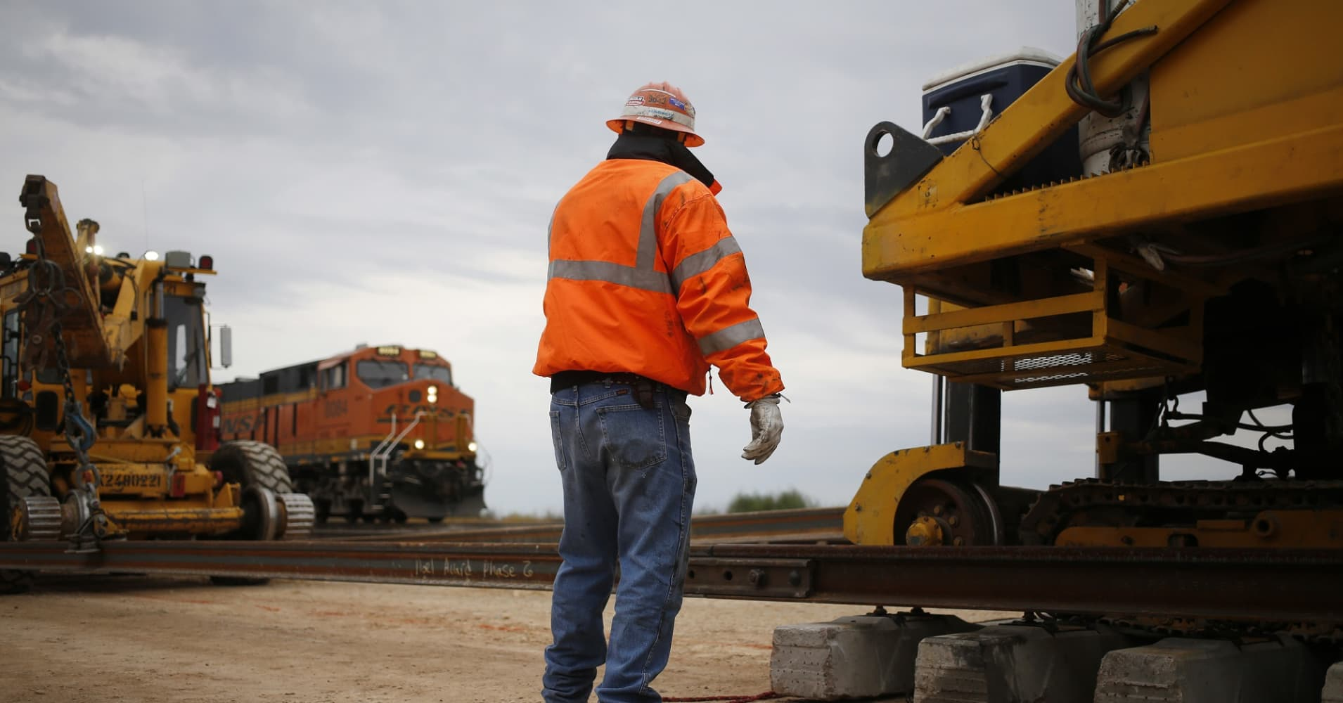 A maintenance-of-way worker watches as an eastbound freight train passes by his track gang in Alva, Oklahoma.